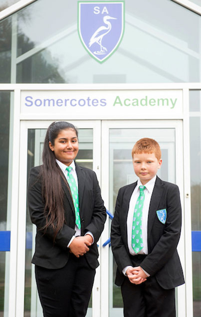 A boy and a girl student stood wearing the academy lower school uniform